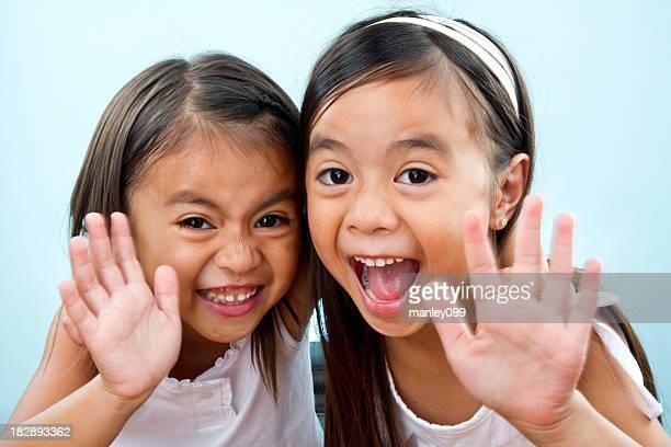 Mignon sisters agitant Bonjour l'objectif