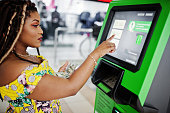 Cute small height african american girl with dreadlocks, wear at coloured yellow dress, withdrawing money dollars from credit card at ATM.