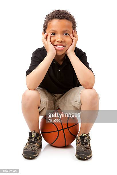 Cute smiling 8-year old mixed race boy sitting on basketball