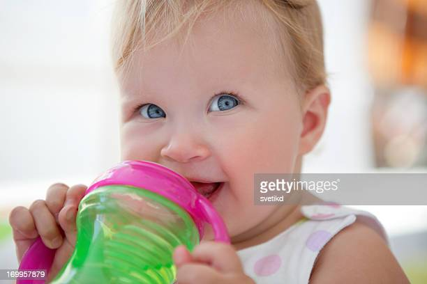 Cute smiling baby drinking water.