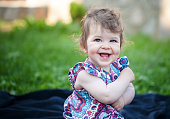 Cute smiling baby girl sitting on the grass
