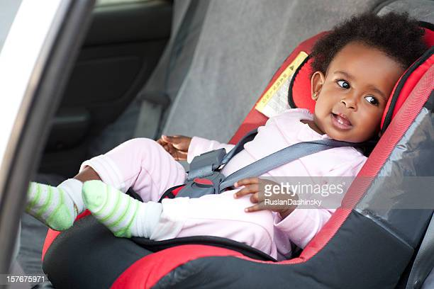 Cute smiling baby strapped in a car seat for safety