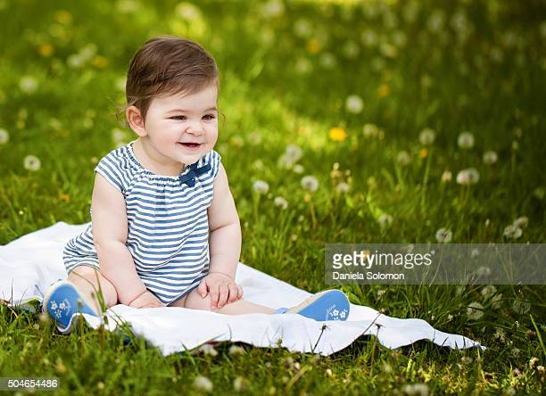 Cute smiling babygirl looking away, sitting on the grass