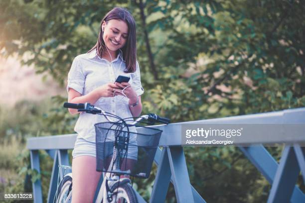 Cute Smiling Female Preparing Playlist For Afternoon Bicycle Ride in City Park