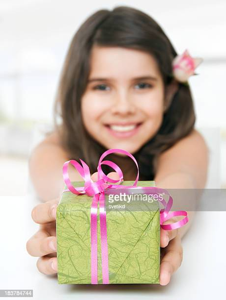 Cute smiling girl holding a gift.