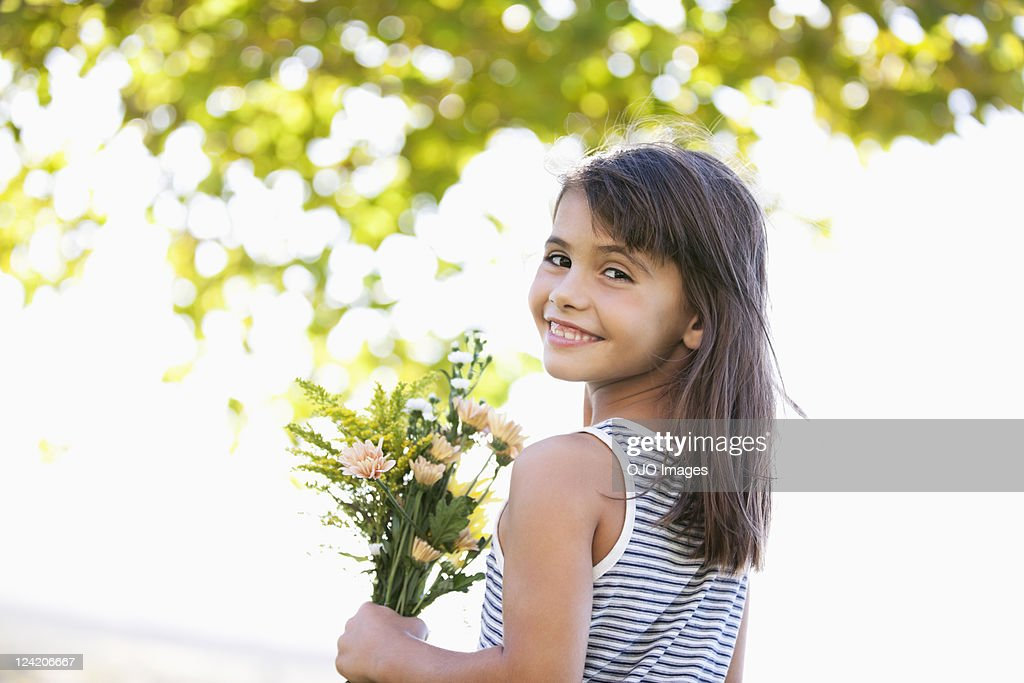 Cute smiling girl holding bunch flower : Stock Photo
