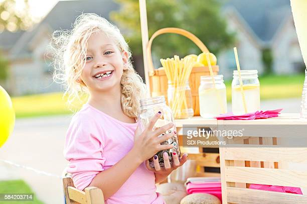 Cute smiling girl holding up her earnings from selling lemonade