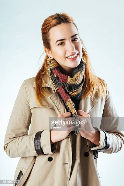 Cute smiling girl in winter fashion with overcoat and scarf
