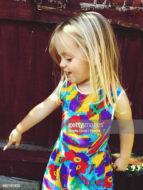 Cute Smiling Girl Pointing Down Against Fence In Yard