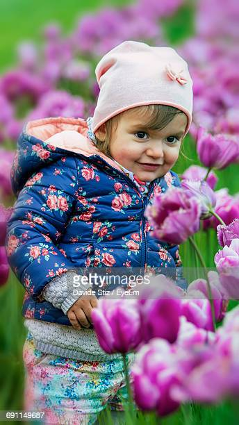 Cute Smiling Girl Standing Amidst Pink Tulips