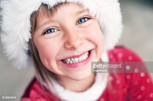 Cute smiling little girl dressed as santa helper