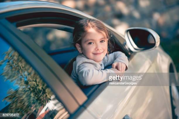 Schattig lachende klein meisje van autoruit poseren