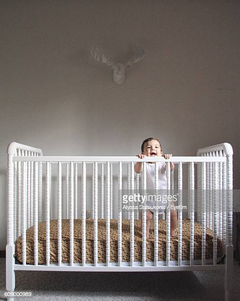 Cute Smiling Toddler Baby Standing In Crib Against Wall At Home