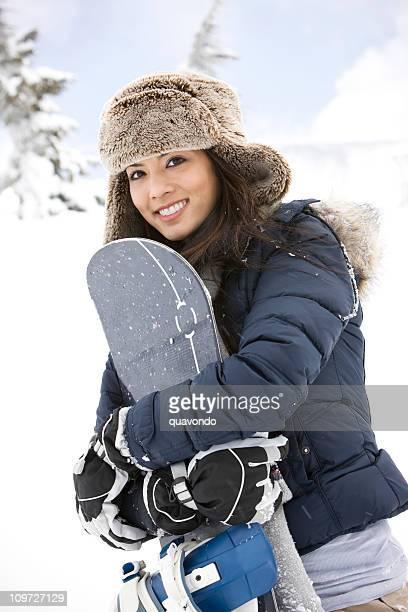 かわいい笑顔の若い女の子保持スノーボードに山
