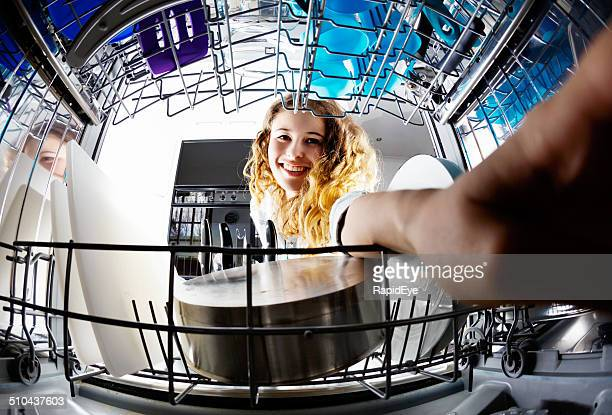 Cute smiling young woman loading or unloading dishwasher