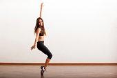 Pretty Latin female dancer rehearsing a tap routine in a dance academy