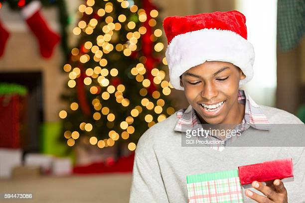 Cute teen boy opens gift on Christmas day