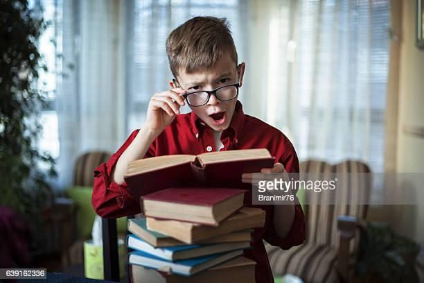 Cute teenage boy with eyeglasses reading a book