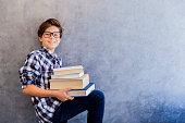 Cute teenage school boy holding books against wall