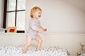Cute toddler boy jumping on the bed in the bedroom.