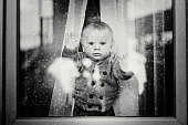 Cute toddler boy, staying at home behind the glass doors or window, watching outside