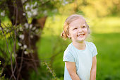 Cute toddler girl outdoors portrait in summer day. Smiling and charming child. Little lady with blonde and curly hair