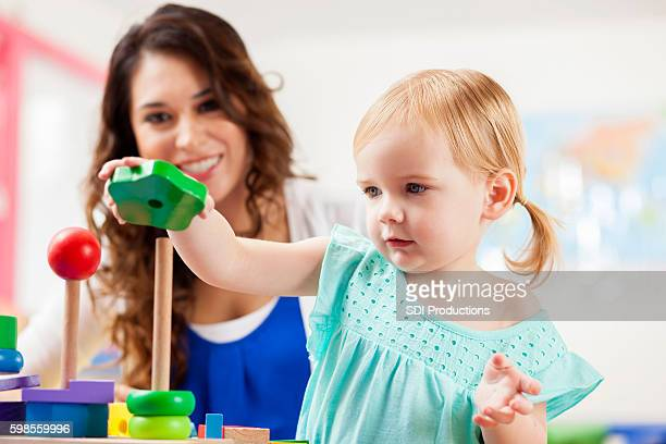 Cute toddler girl playing with learning blocks in daycare