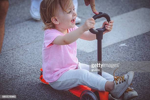 Cute toddler girl rides push scooter on the promenade