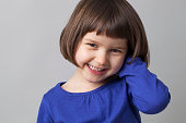portrait of young happy preschool girl smiling in front of the camera for happiness