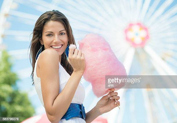 Cute Woman eating Cotton Candy at the Funfair
