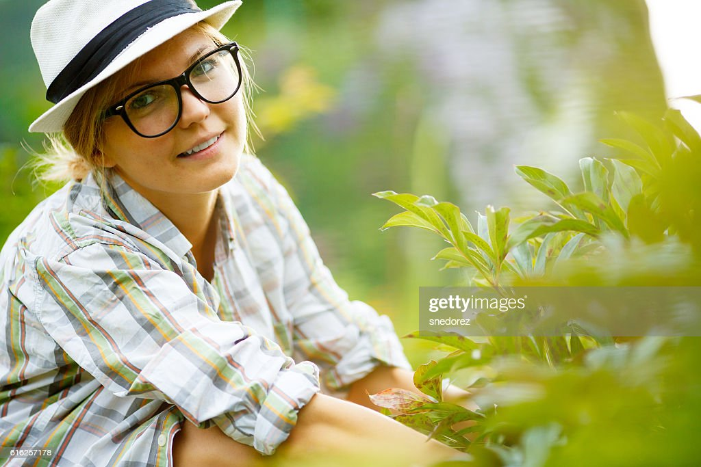 Cute woman gardener in hat and glasses working in garden : Foto de stock