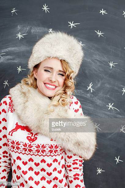 Cute woman in winter outfit, wearing fur cap and shawl