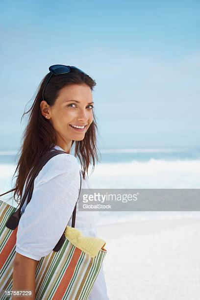 Cute woman out on a beach picnic with bag