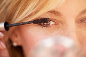 Cute middle age woman putting some mascara on