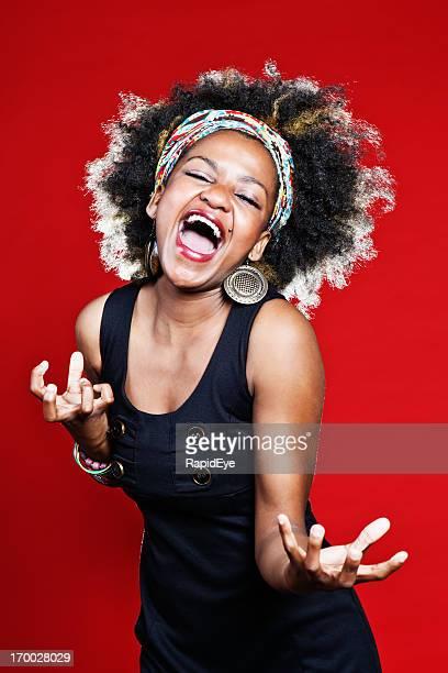 Jolie femme avec Coiffure Afro chante, danses et des rires contre rouge