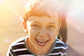 cute young 6-7 years old boy smiles, sunny lights, childhood concept