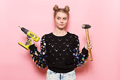 cute young adult woman holding working tools in hands.
