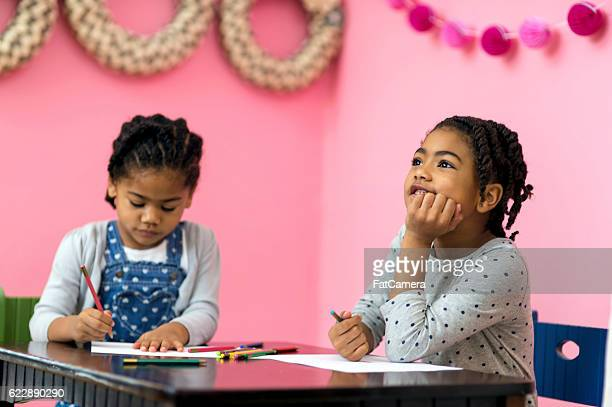 Cute young african american girls drawing pictures with colored pencils