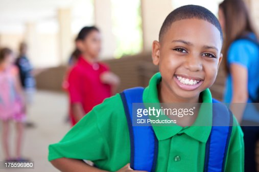 Cute young boy smiling at school campus
