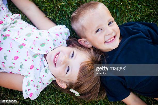 Cute Young Children Smiling on Grass