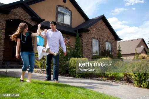 Cute Young Couple and Child with Beautiful Home