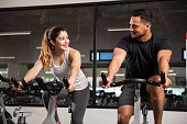 Beautiful young Hispanic woman flirting and talking to a guy while they both do some exercising at a gym