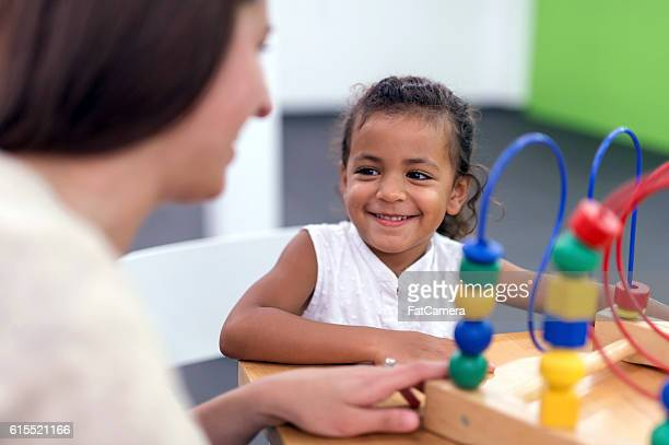 Cute young ethnic girl smiling at her therapist