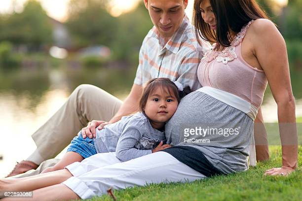 Cute young family sitting on the grass in a park
