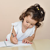 Cute young girl drawing with a pencil in the notebook