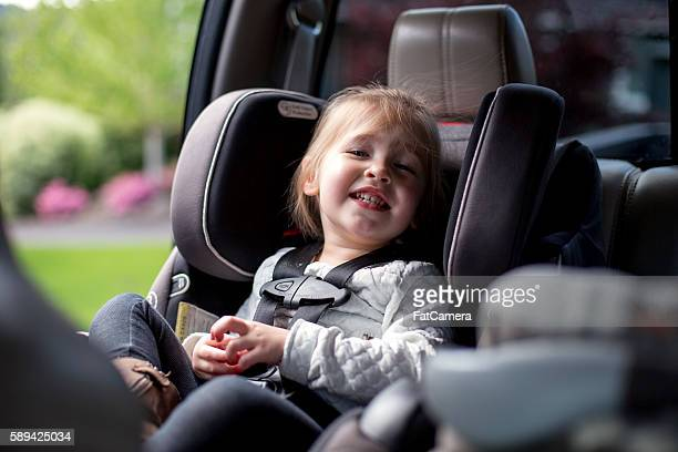 Cute young girl smiling in her car seat