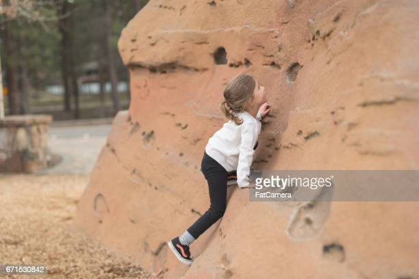 Cute young girl tries to scale a rock climbing wall at playground outside