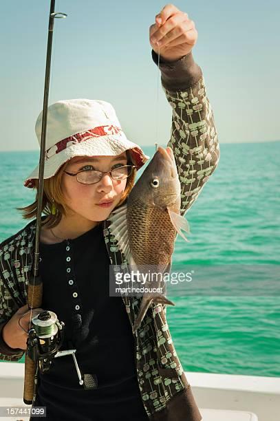 Jolie jeune fille avec une belle prise de pêche, verticale.