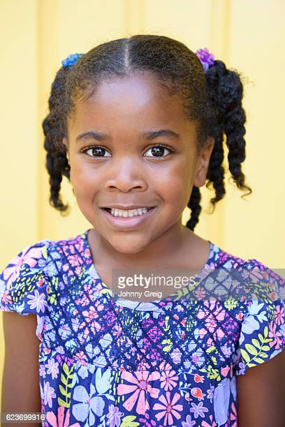 Cute young girl with braids in her hair, smiling