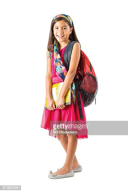 Cute young Hispanic girl holding book and backpack before school